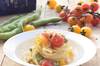 Spaghettone con gamberi fave e pomodorini gialli